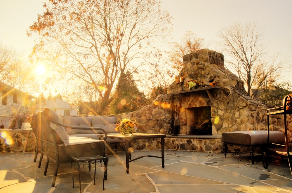Low-angle view of a flagstone patio with an outdoor stone fireplace
