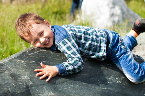 a young boy playing on a boulder in his backyard