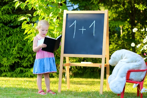 Young girl drawing on a chalkboard outside
