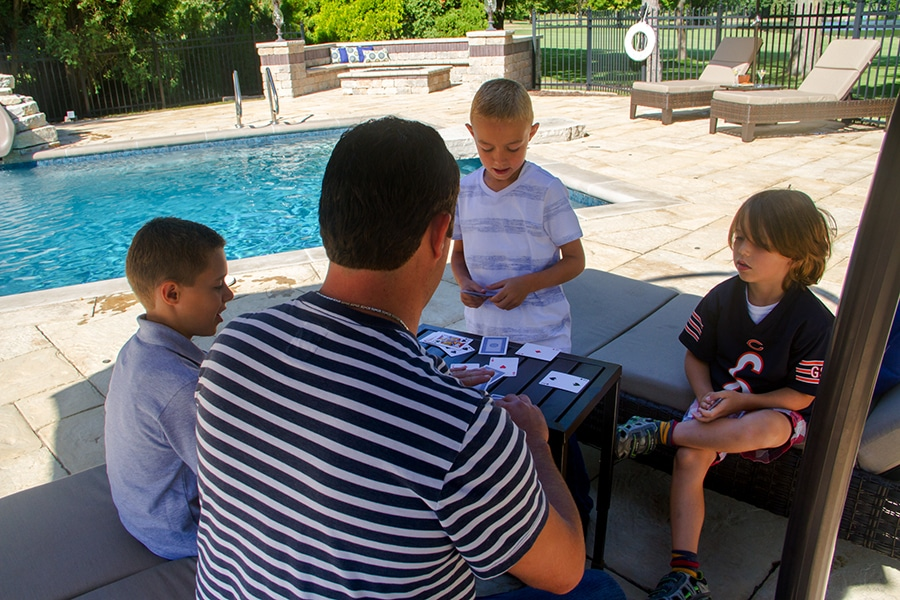 Playing a game of cards on the brick paver pool deck