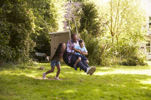 Family having fun on a tire swing