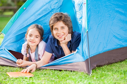 two young sibling having fun in a tent