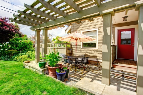 wooden pergola creating shade on a hot day over a brick patio