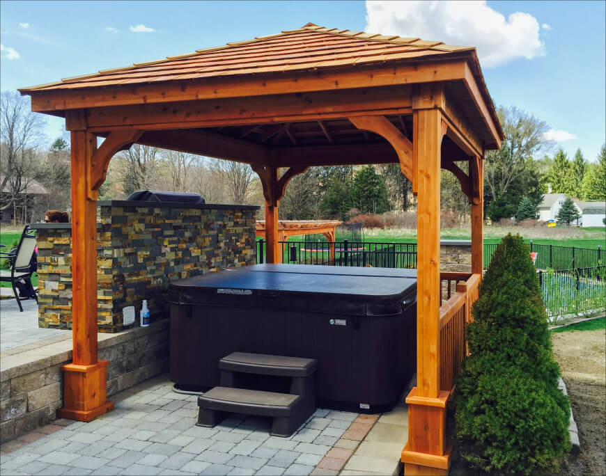 Hot tub on brick paver patio with a pavilion over top